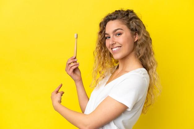 Молодая кавказская женщина, держащая чистку зубов изолирована на желтом фоне, указывая назад