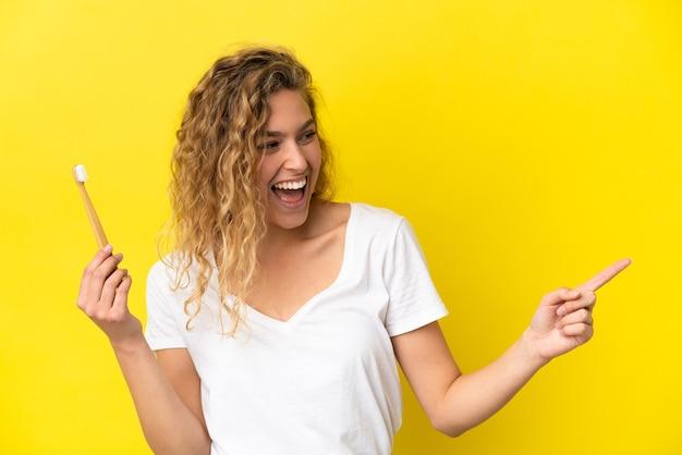 横に指を指し、製品を提示する黄色の背景に分離されたブラッシング歯を保持している若い白人女性