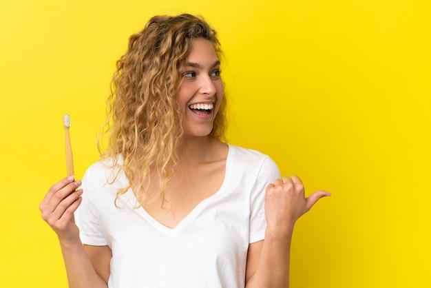 製品を提示する側を指している黄色の背景に分離されたブラッシング歯を保持している若い白人女性