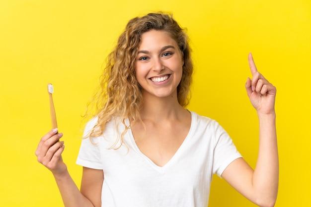 素晴らしいアイデアを指している黄色の背景に分離されたブラッシング歯を保持している若い白人女性