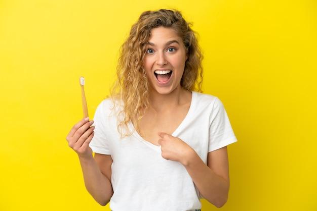 驚きの表情で黄色の背景に分離されたブラッシング歯を保持している若い白人女性