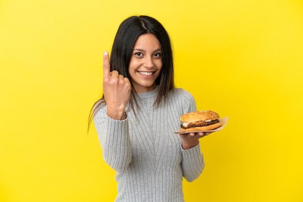 来るジェスチャーをしている黄色の背景に分離されたハンバーガーを保持している若い白人女性