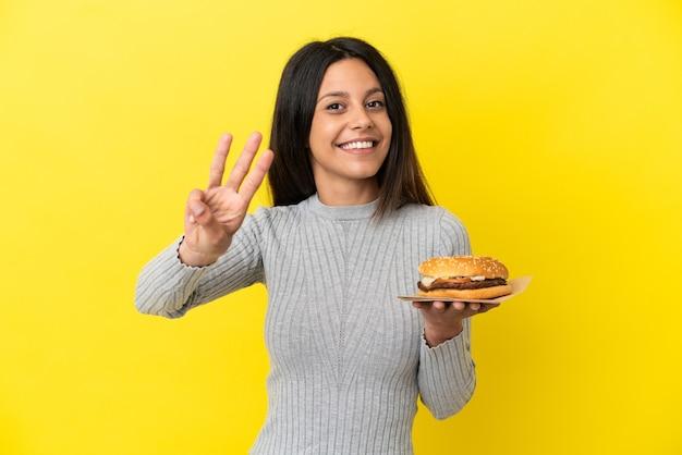 幸せな黄色の背景に分離されたハンバーガーを保持し、指で3を数える若い白人女性