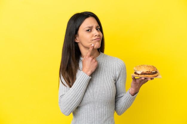 Молодая кавказская женщина, держащая гамбургер на желтом фоне, сомневается, глядя вверх