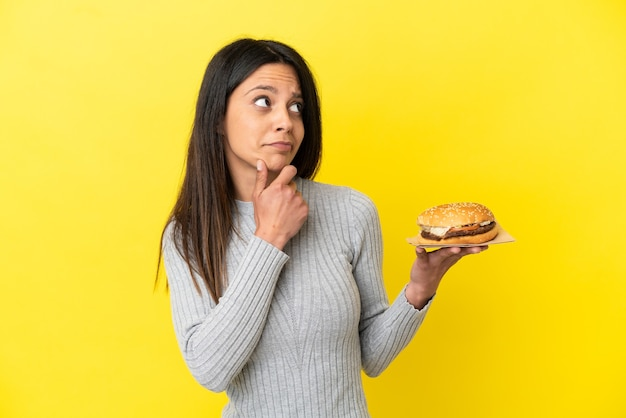 Молодая кавказская женщина, держащая гамбургер на желтом фоне с сомнениями