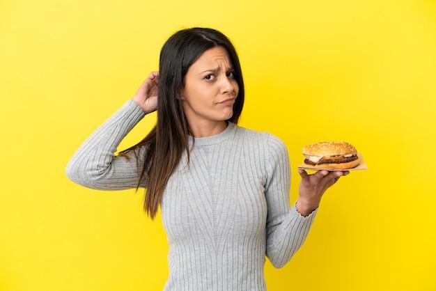 疑いを持って黄色の背景に分離されたハンバーガーを保持している若い白人女性