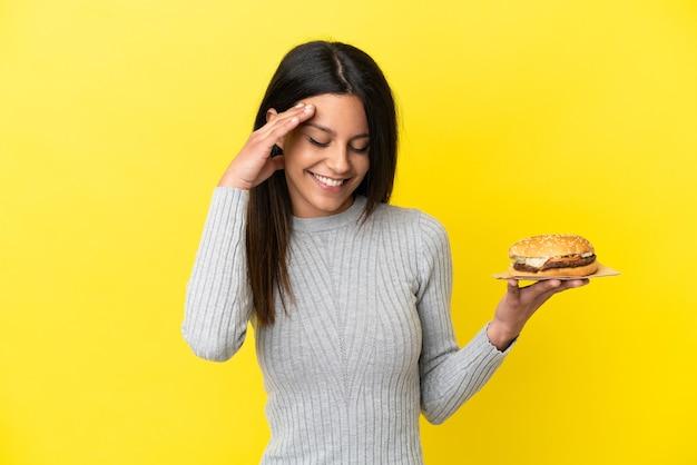 Молодая кавказская женщина, держащая гамбургер на желтом фоне смеясь