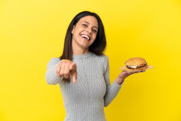 Молодая кавказская женщина, держащая гамбургер изолирована на желтом фоне, указывая вперед с счастливым выражением лица