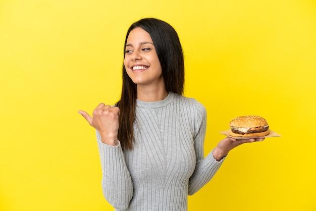 Молодая кавказская женщина держит гамбургер на желтом фоне, указывая в сторону, чтобы представить продукт