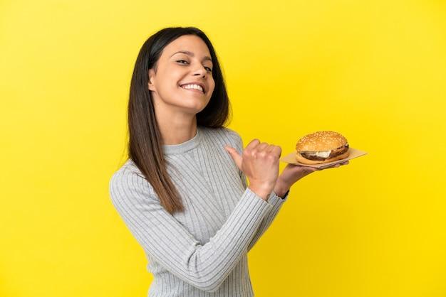 Молодая кавказская женщина, держащая гамбургер на желтом фоне, гордая и самодовольная