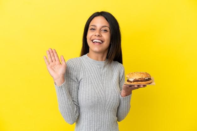 Молодая кавказская женщина, держащая гамбургер на желтом фоне, салютует рукой с счастливым выражением лица