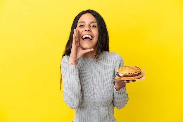 Молодая кавказская женщина, держащая гамбургер, изолированная на желтом фоне, кричит с широко открытым ртом