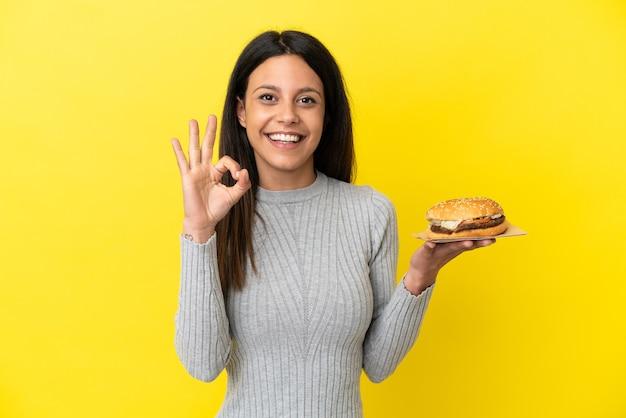 指でokサインを示す黄色の背景に分離されたハンバーガーを保持している若い白人女性