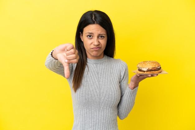 Молодая кавказская женщина, держащая гамбургер на желтом фоне, показывает палец вниз с негативным выражением лица
