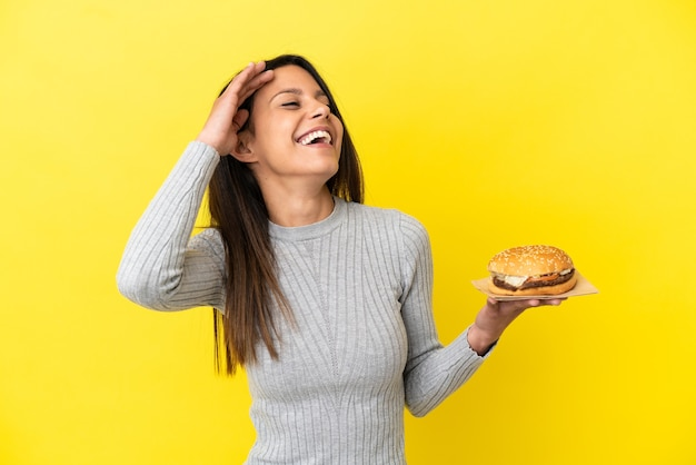 Молодая кавказская женщина, держащая гамбургер на желтом фоне, много улыбаясь