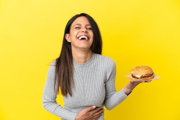 たくさん笑って黄色の背景に分離されたハンバーガーを保持している若い白人女性