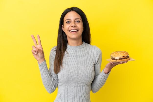 Молодая кавказская женщина, держащая гамбургер на желтом фоне, улыбается и показывает знак победы
