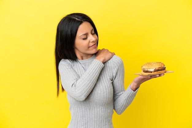 努力したために肩の痛みに苦しんで黄色の背景に分離されたハンバーガーを保持している若い白人女性