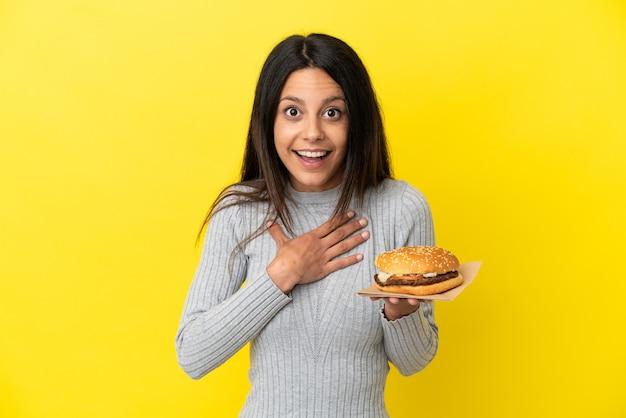 黄色の背景で隔離のハンバーガーを保持している若い白人女性は、右を見ながら驚いてショックを受けました