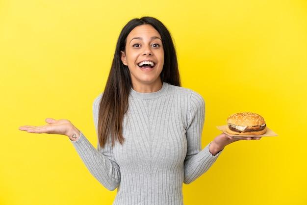 Молодая кавказская женщина держит гамбургер на желтом фоне с шокированным выражением лица