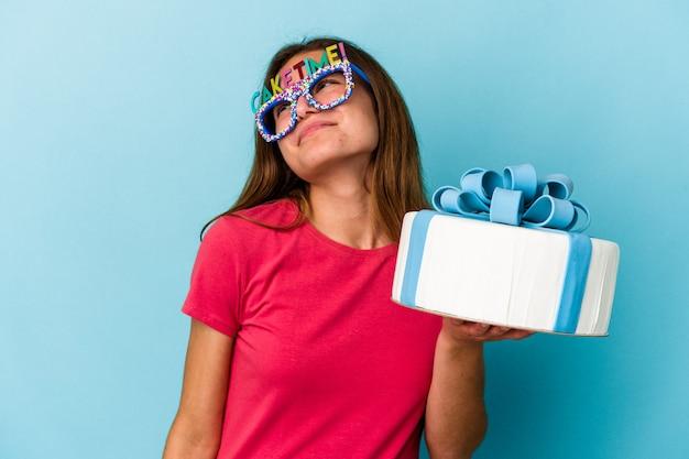 목표와 목적을 달성하는 꿈을 꾸고 파란색 배경에 고립 된 케이크를 들고 젊은 백인 여자