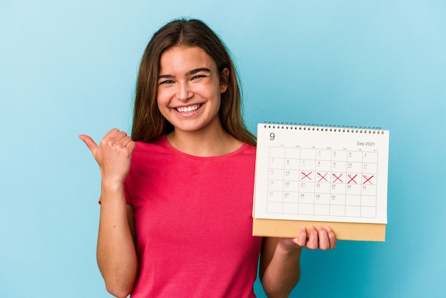 Молодая кавказская женщина, держащая календарь на розовом фоне, улыбается и поднимает большой палец вверх