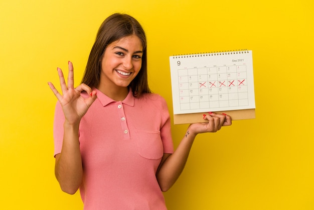 Молодая кавказская женщина, держащая календарь, изолированный на желтом фоне, веселый и уверенный, показывая одобренный жест.