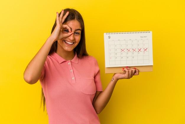 Молодая кавказская женщина, держащая календарь, изолированный на желтом фоне, взволнована, держа на глазах хорошо жест.
