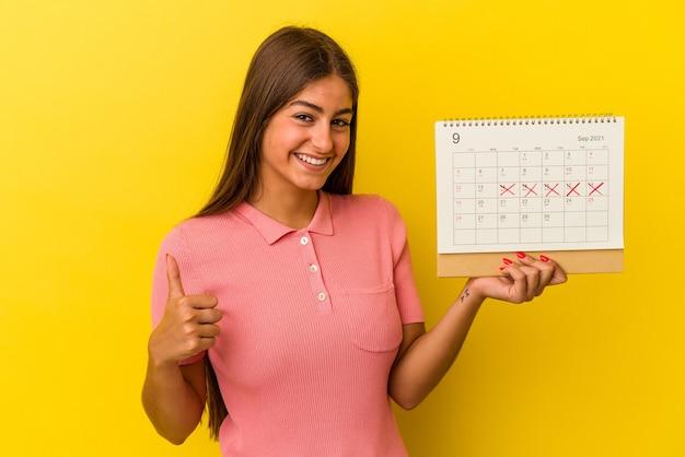 Молодая кавказская женщина, держащая календарь на желтом фоне, улыбается и поднимает палец вверх