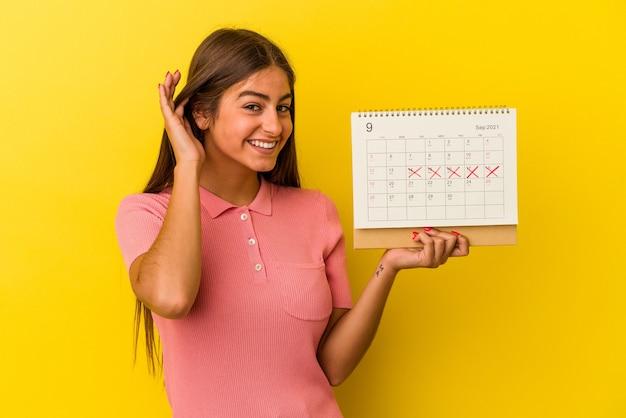 ゴシップを聴こうとしている黄色の背景で隔離のカレンダーを保持している若い白人女性。
