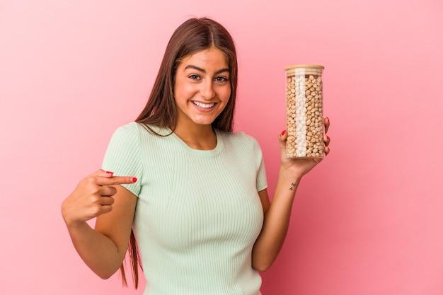誇りと自信を持って、シャツのコピースペースを手で指しているピンクの背景の人に分離されたひよこ豆の瓶を保持している若い白人女性