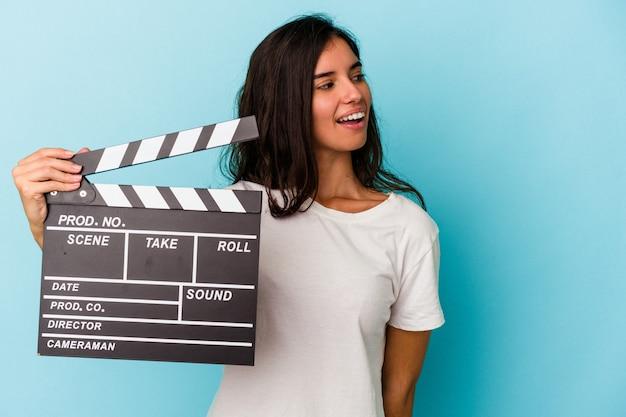 青い背景で隔離のカチンコを保持している若い白人女性は、笑顔、陽気で楽しい脇に見えます。