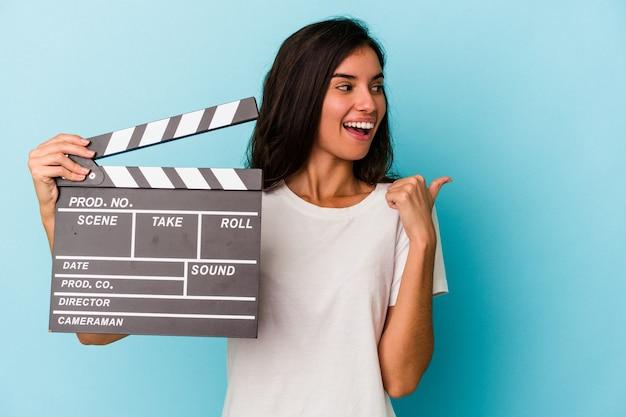 青い背景に隔離されたカチンコを持っている若い白人女性は、親指の指を離して、笑ってのんきなポイント。