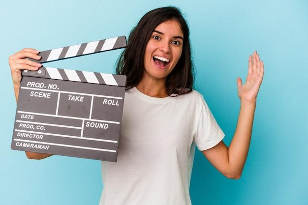 青い背景に分離されたカチンコを持っている若い白人女性は、嬉しい驚きを受け取り、興奮し、手を上げます。