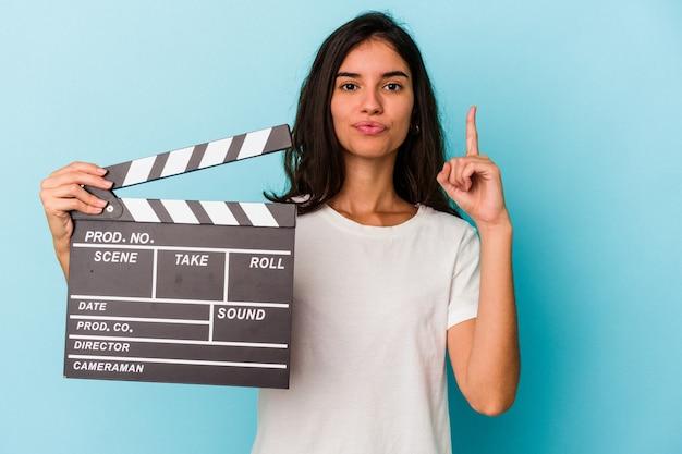 Молодая кавказская женщина, держащая с 'хлопушкой', изолированную на синем фоне, показывая номер один пальцем.