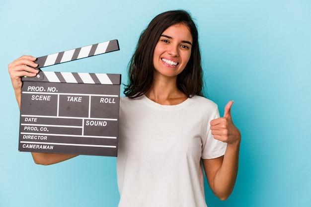 青い背景に分離されたカチンコを持って笑顔と親指を上げる若い白人女性