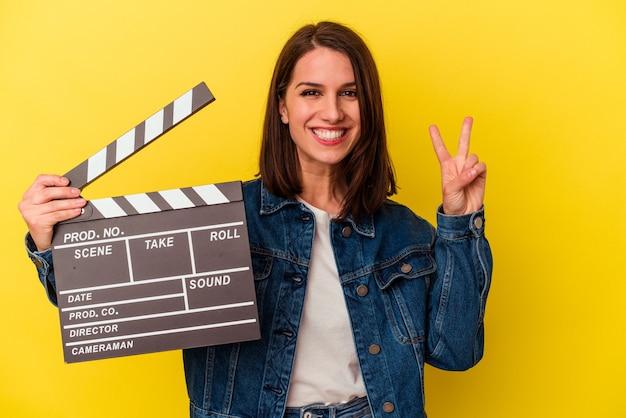 Молодая кавказская женщина, держащая с 'хлопушкой', изолированную на желтом фоне, показывает номер два пальцами.