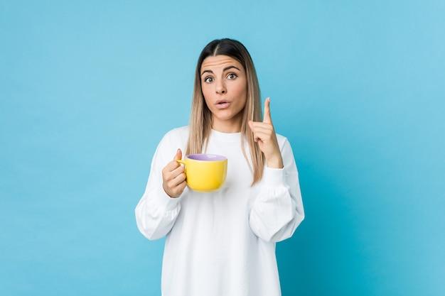 いくつかの素晴らしいアイデア、創造性の概念を持っているコーヒーカップを保持している若い白人女性。