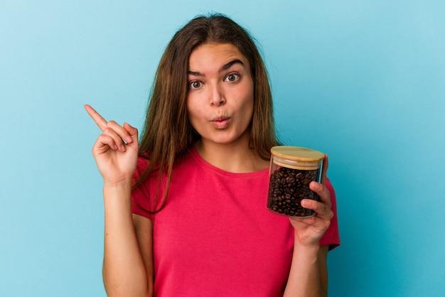 いくつかの素晴らしいアイデア、創造性の概念を持つ青の背景に分離されたコーヒーの瓶を保持している若い白人女性。
