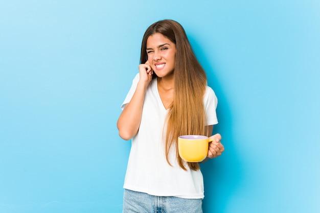 Молодая кавказская женщина, держащая кружку кофе, закрывая уши руками.