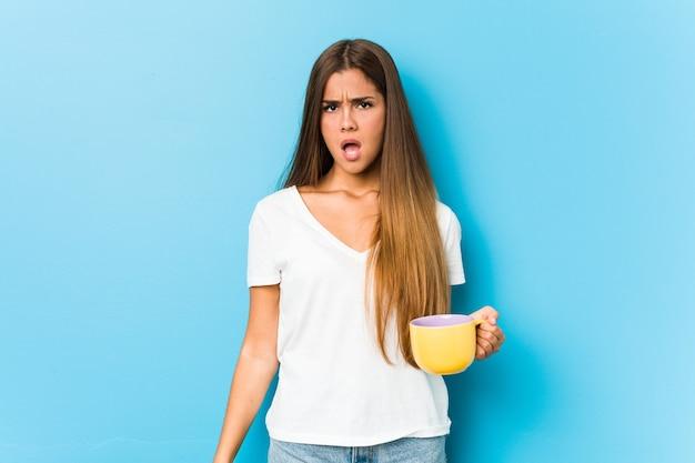 매우 화가 공격적 비명 커피 잔을 들고 젊은 백인 여자.