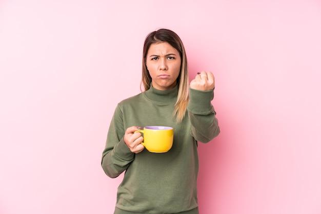Молодая кавказская женщина, держащая кофе, показывая кулак, агрессивное выражение лица.