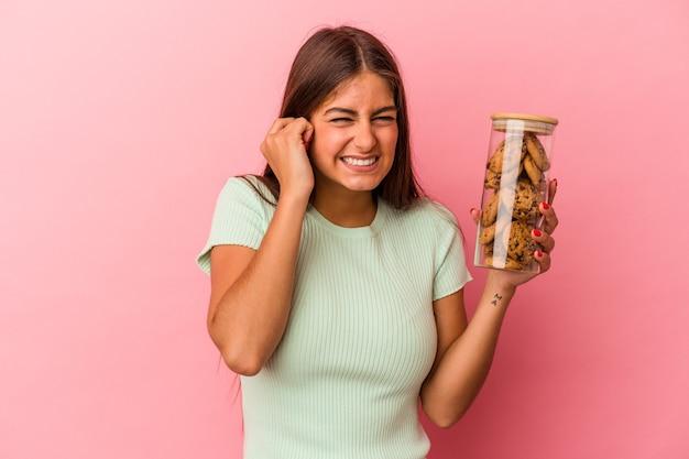 手で耳を覆うピンクの背景に分離されたクッキーの瓶を保持している若い白人女性。