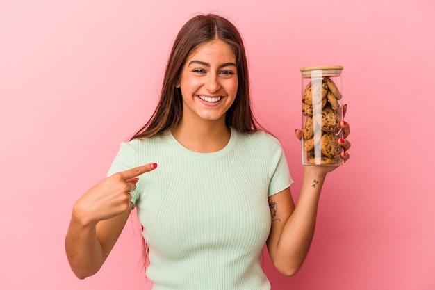 誇りと自信を持って、シャツのコピースペースを手で指しているピンクの背景の人に分離されたクッキーの瓶を保持している若い白人女性