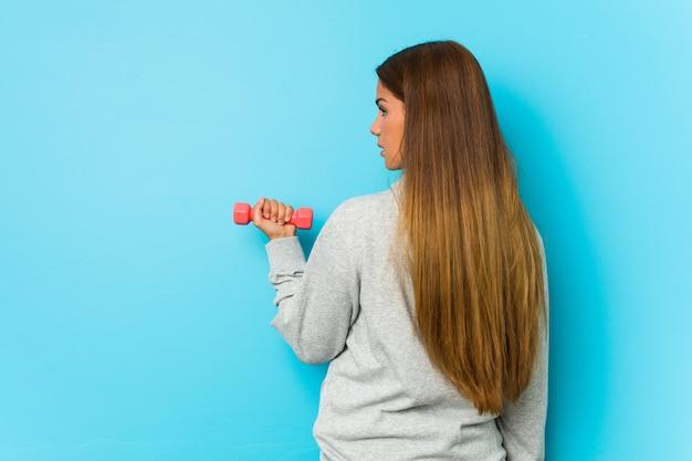 青で隔離のダンベルを保持している若い白人女性