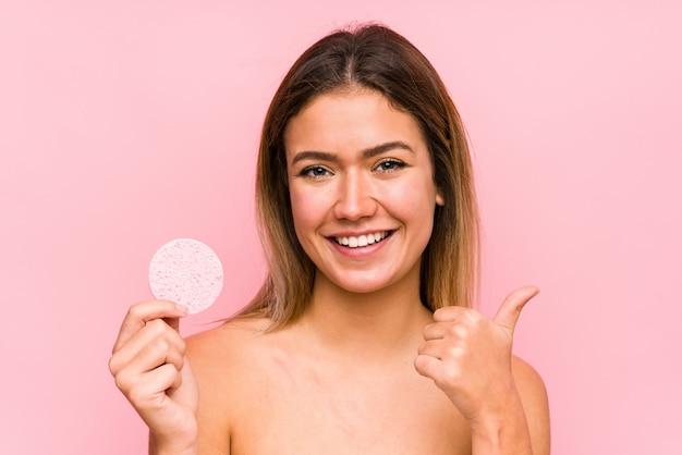 笑顔と親指を上げる分離された顔のディスクを保持している若い白人女性
