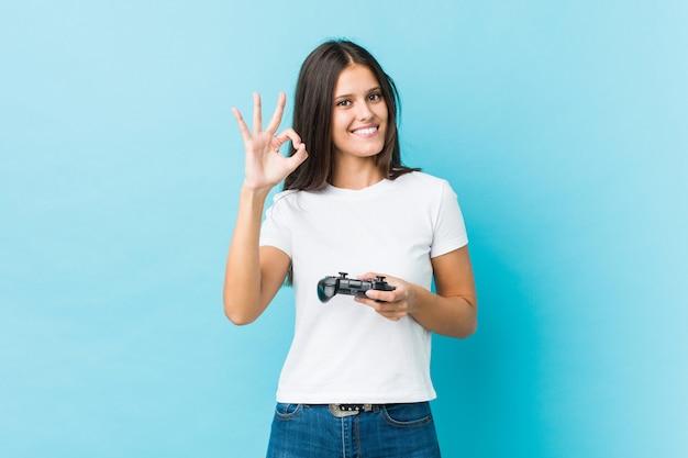 Молодая кавказская женщина держа регулятор игры жизнерадостный и уверенно показывая одобренный жест.
