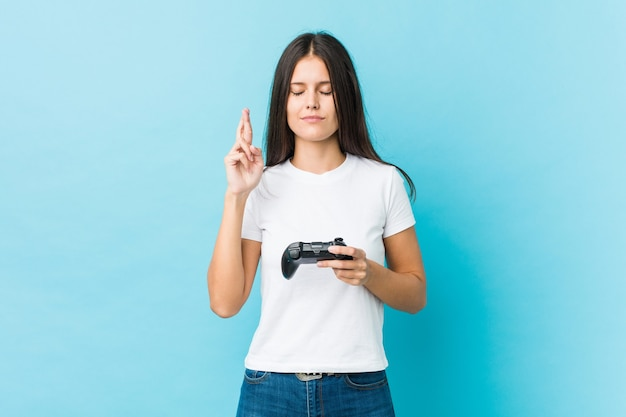 Молодая кавказская женщина, держащая игровой контроллер, скрещивает пальцы за удачу