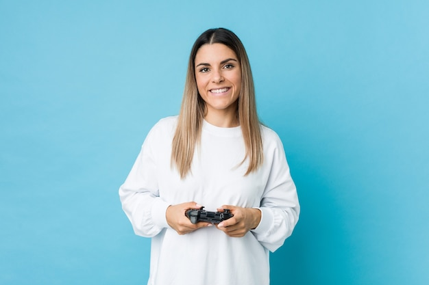 Молодая кавказская женщина, держащая игровой контроллер, счастливая, улыбающаяся и веселая.