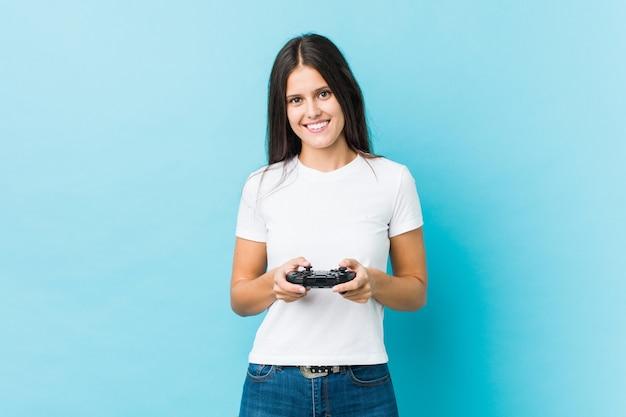 Молодая кавказская женщина держа игровой контроллер счастливым, усмехаясь и жизнерадостным.